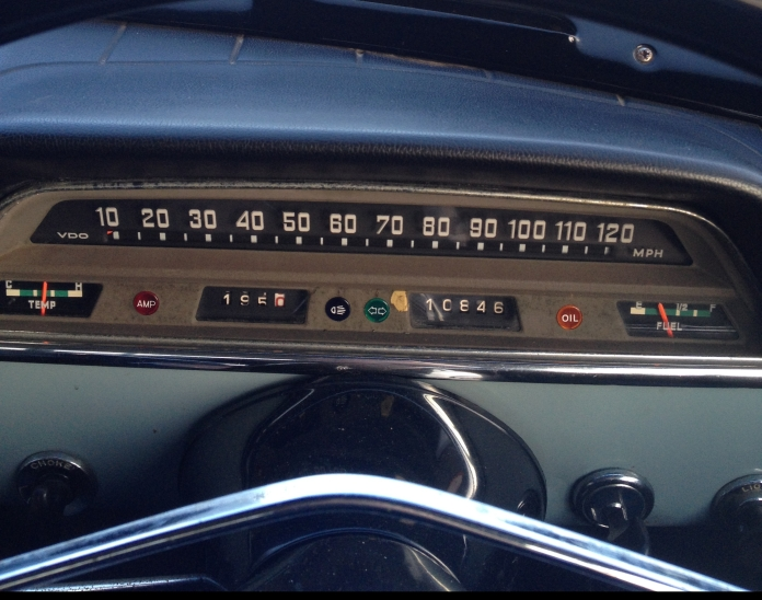 A 1967 Volvo Amazon speedometer and dashboard, with a straight, clear road ahead.